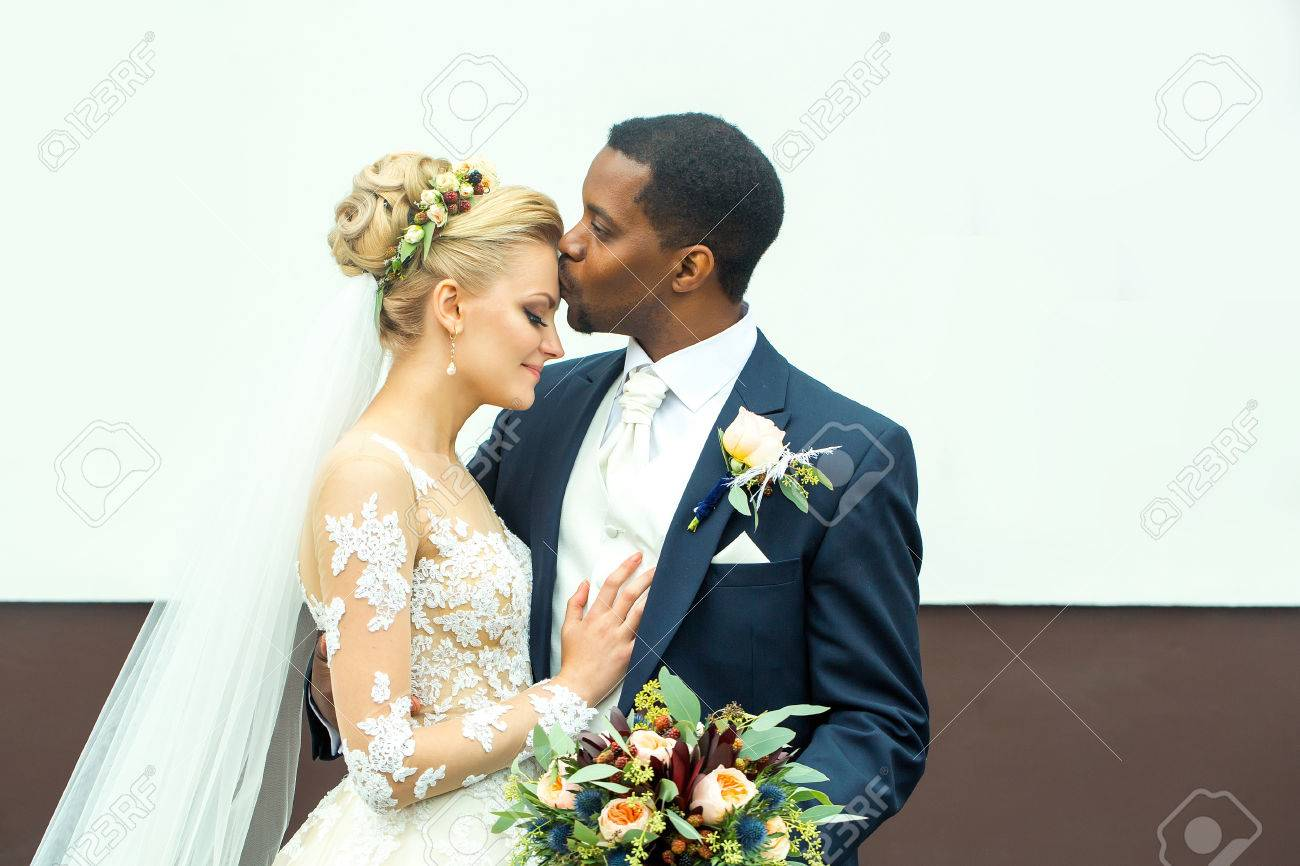 Young man elegant african American groom kisses tenderly beautiful woman happy bride in white dress and veil married couple on wedding day - 64986071