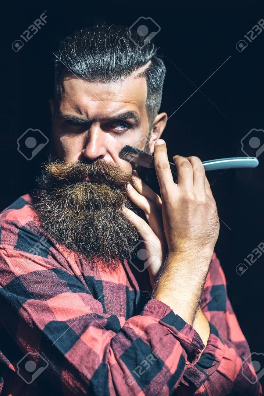 Banque d\u0027images , Jeune hipster homme avec le visage barbu belle tenue,  coupe rasoir gorge près de la barbe longue de la mode et la moustache sur  le noir
