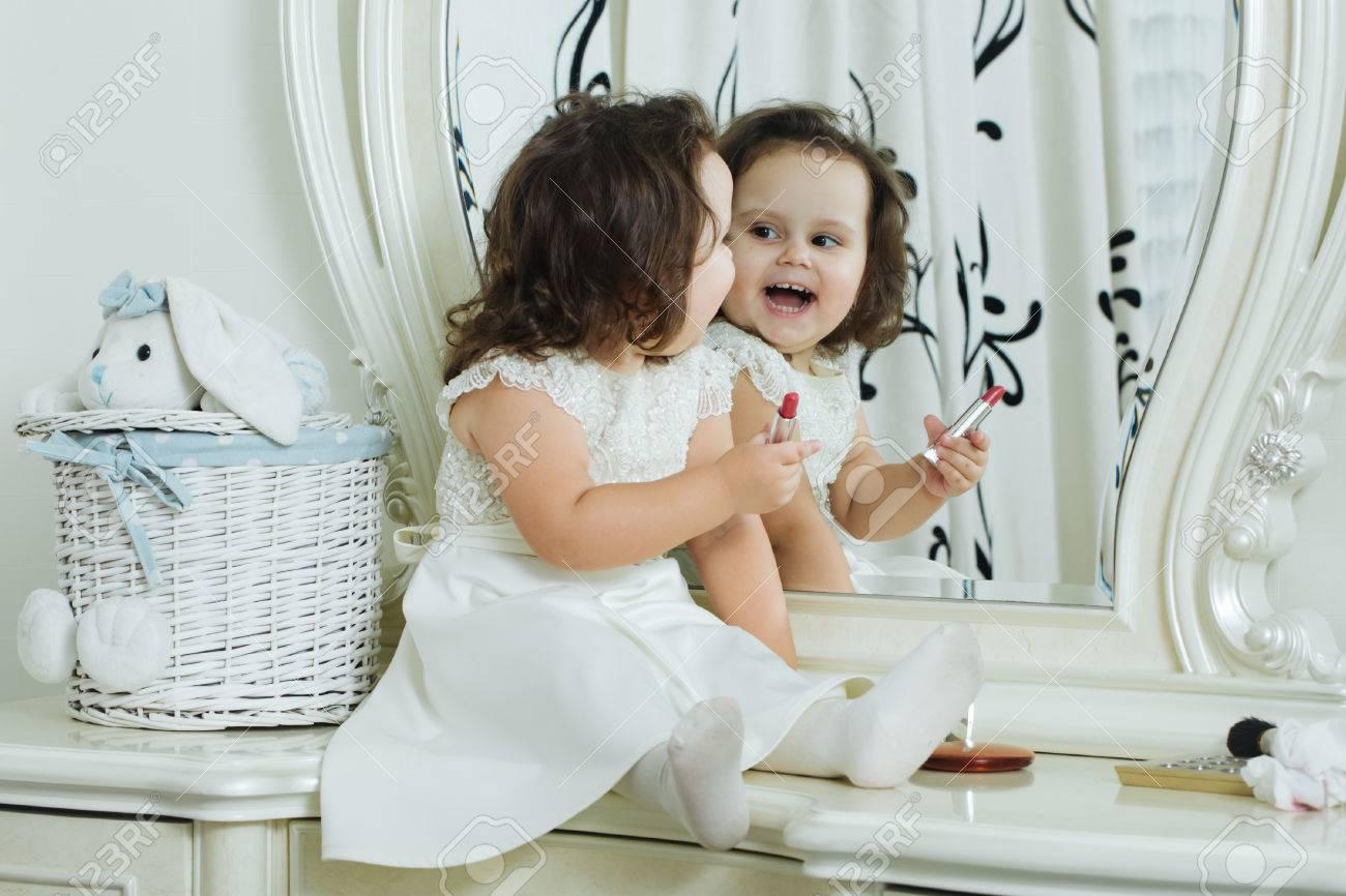 50fb84aa3f8e4 Banque d images - Mignon petite fille joue avec le rouge à lèvres rouge  devant le miroir. Adorable bébé joue avec maquillage kit