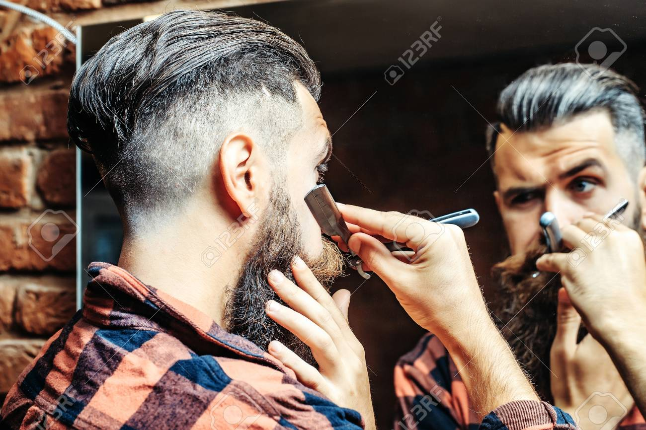 Handsome bearded man hipster with stylish haircut and beard holding