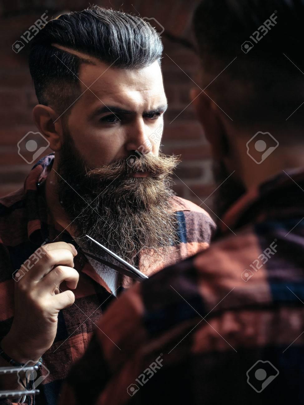 Banque d\u0027images , Hipster jeune homme avec beau visage barbu brune coupe  barbe de la mode longue avec des ciseaux à la recherche dans le miroir