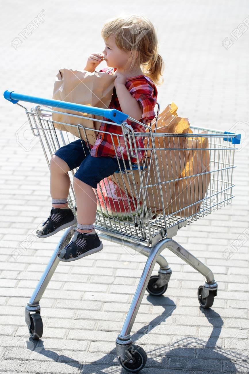 08bb0cd7aad50b Nettes Baby blond Kind in karierten Hemd sitzt im Einkaufswagen und isst  Plätzchen aus Papier Paket