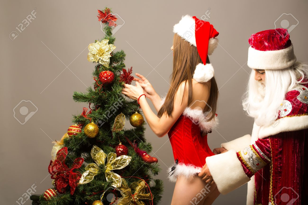santa claus man touches fur on red dress of pretty