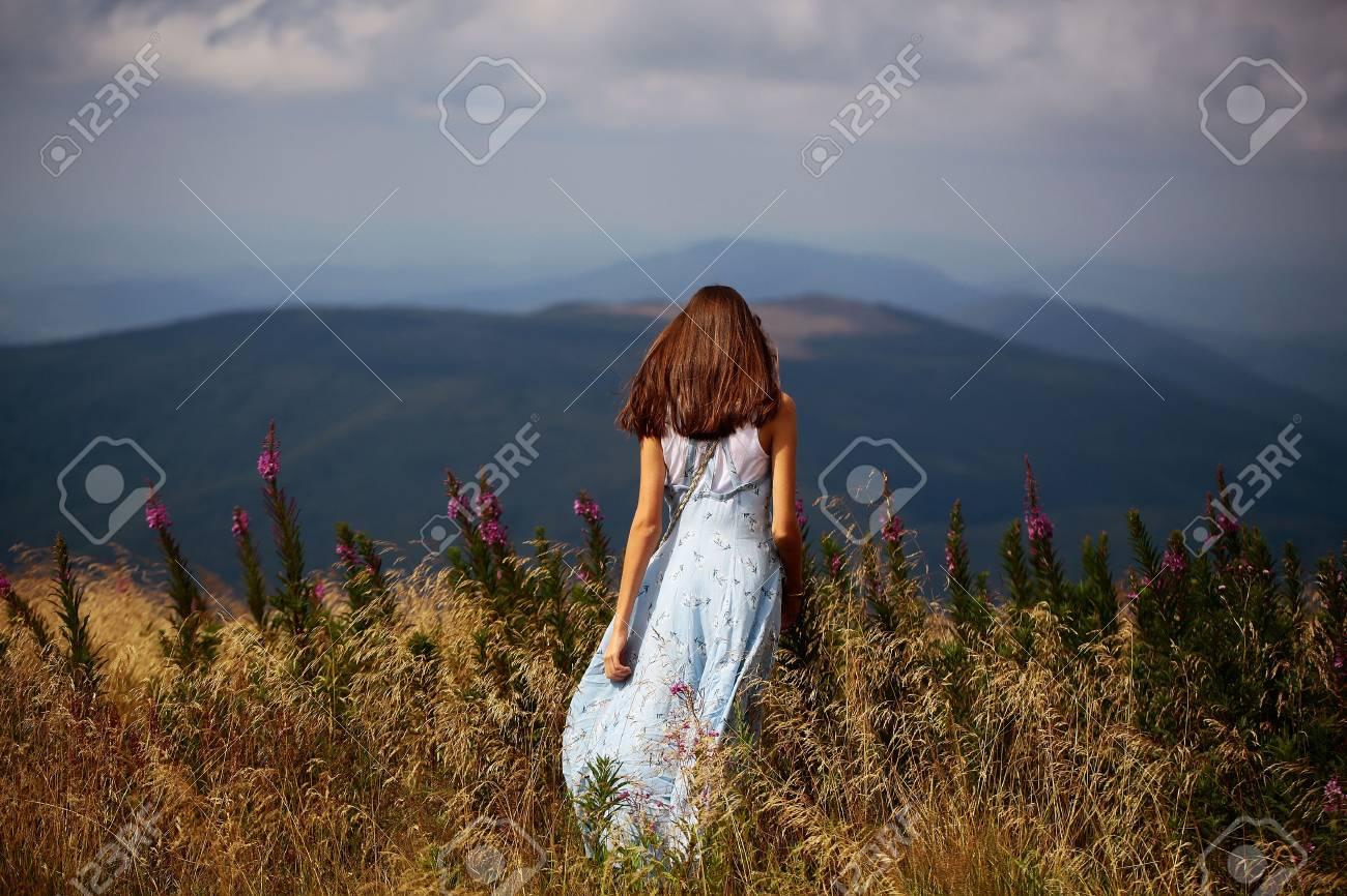 Pretty cute brunette woman or girl stands back in blue dress waving on wind outdoor on beautiful landscape - 64743602
