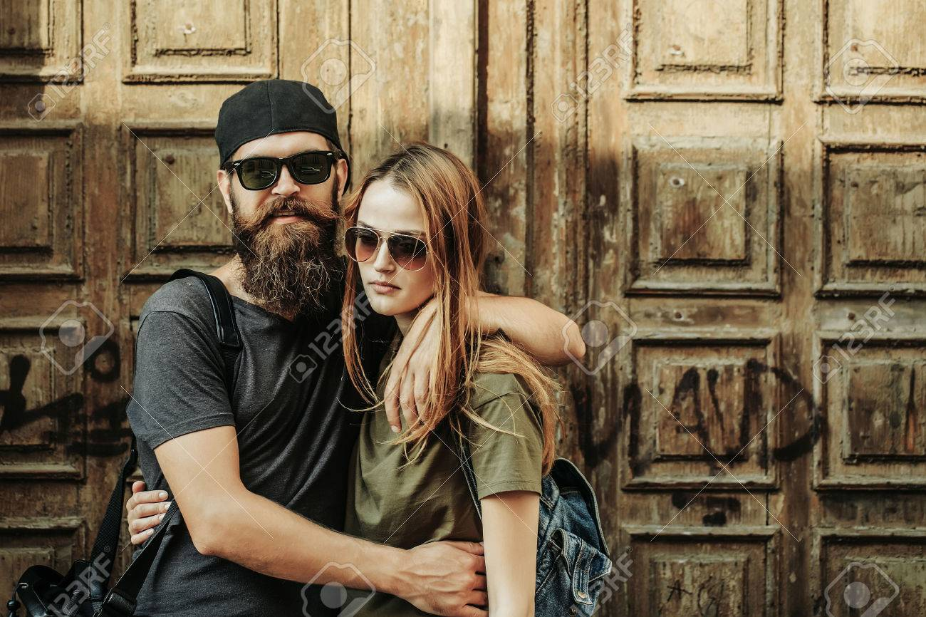 Young man hipster with beard on handsome face in sunglasses and baseball cap hugging pretty girl in casual clothes on wooden door background - 65086249
