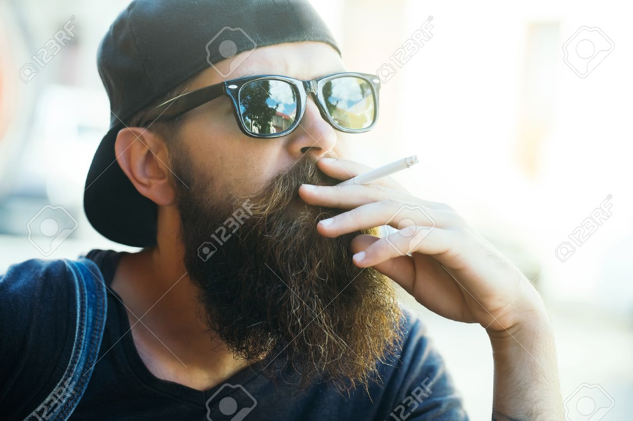 Stock Photo - Young man hipster with long beard on handsome face in black  sunglasses and baseball cap smoking cigarette on light background outdoor 4e466be185b