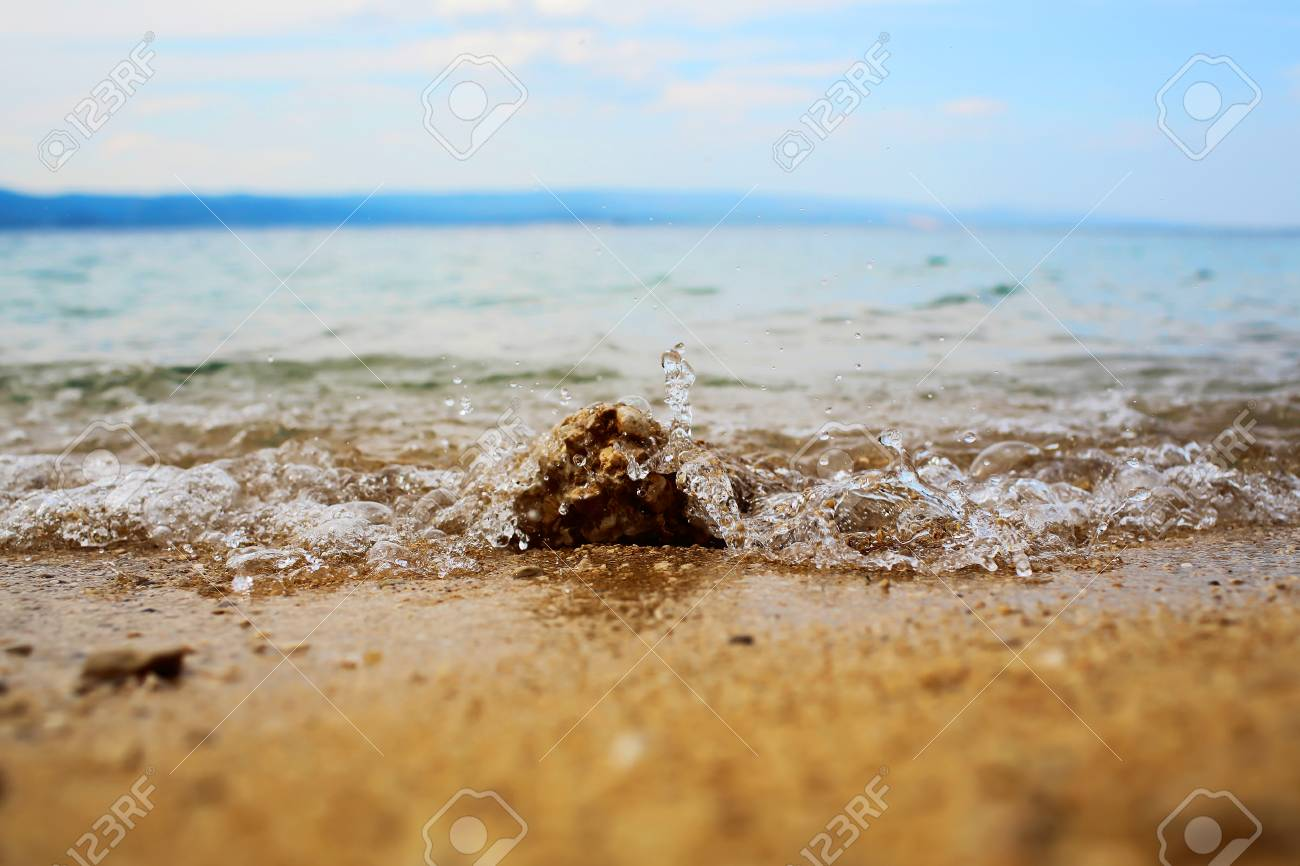 Crystal blue sea or ocean water with ripples low waves hits stones on shore  beach on 7a5c6c72d