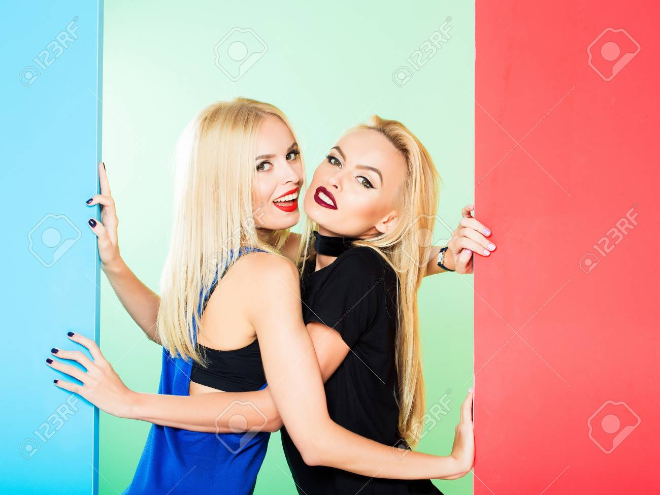 Pretty cute girls or beautiful blond women twins in sexy dress with red  lips and long