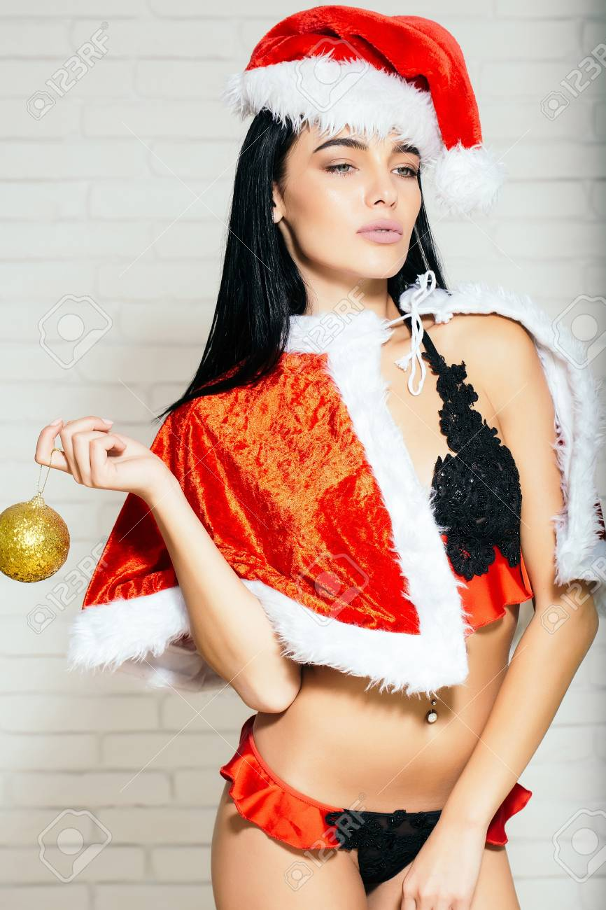 ef62b622a young sexy new year woman or cute girl with brunette hair and pretty face  in red christmas santa claus holiday hat coat and lace lingerie holds  golden ...