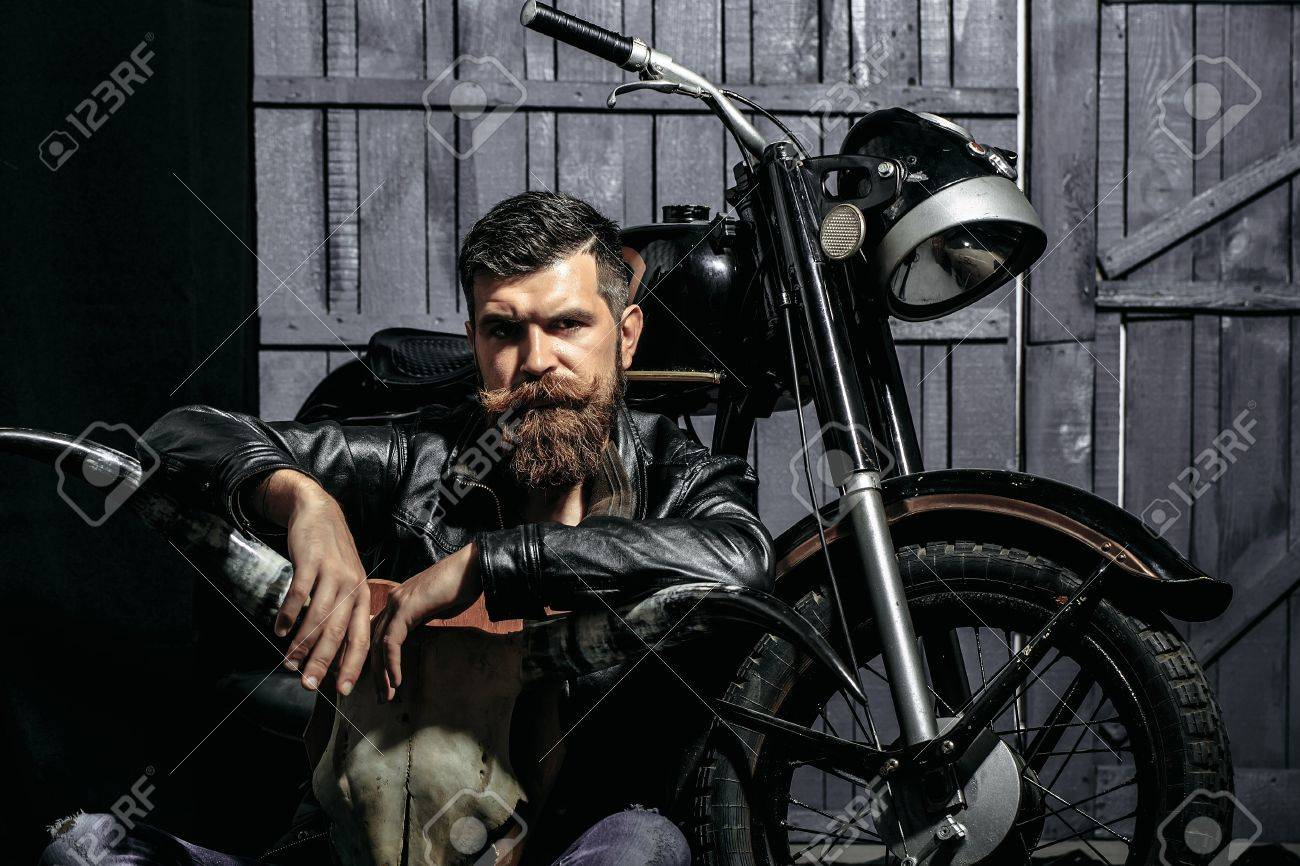 Bearded man hipster biker brutal male with beard and moustache in leather jacket sits on floor near motorcycle with bone skull antlers on wooden background - 67317755