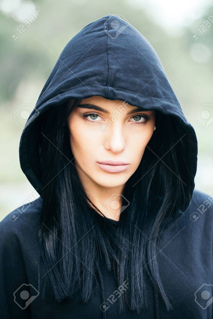 Stock Photo - young pretty woman or fashionable sexy girl with cute face  and brunette hair in black jacket with hood outdoor on blurred or defocused  ...