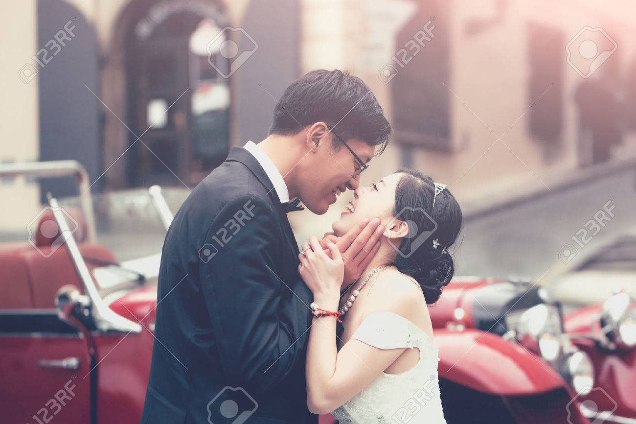 Chinese cute bride and groom young newlyweds just married couple kiss on streets of old city on wedding day in long white wedding dress stands outdoors near red retro car - 66445097