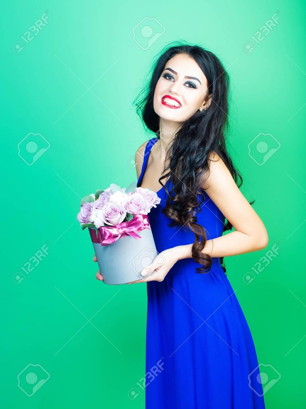 7b2fcfc11 Joven Mujer Muy Sexy O Niña Con Cara Sonriente Linda Y Cabello Largo Morena  Tiene Maquillaje De Moda Con Lápiz Labial Rojo En Vestido Azul Tiene Ramo  De ...