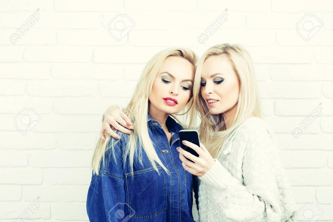 Chicas Bonitas O Dos Mujeres Atractivas Con El Pelo Rubio Y El Maquillaje Hermoso Jugar Con El Teléfono Inteligente Móvil En La Pared De Ladrillo