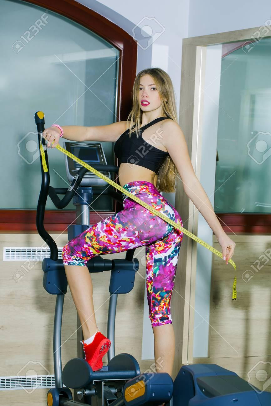 Hübsches Mädchen oder schöne Frau mit langen blonden Haaren in rosa  Sportbekleidung mit fit, schlank, sexy, Körper, Übungen auf Crosstrainer,  hält