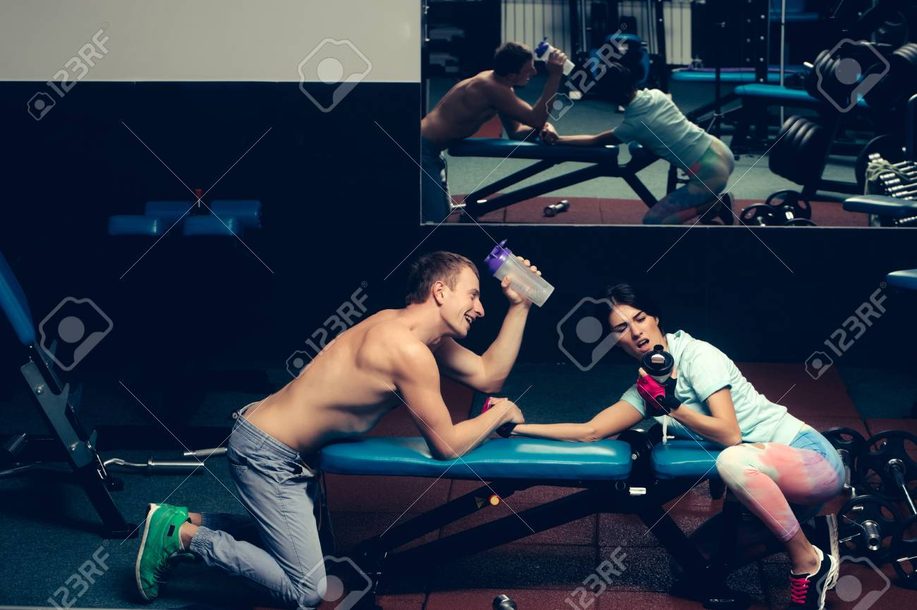 arm wrestling happy couple of pretty woman or cute girl and handsome