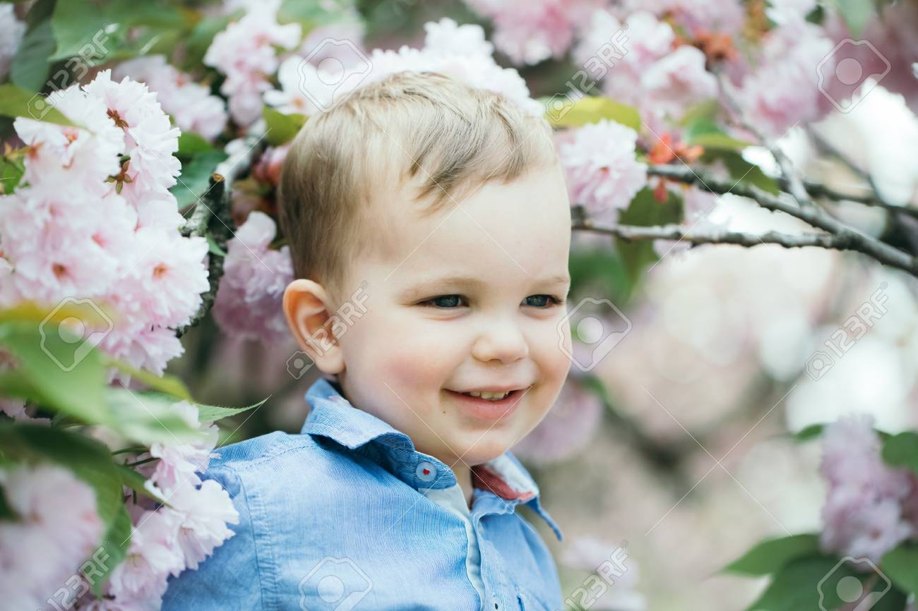 f57ffa618792 Cute happy baby boy, little child, with blond hair in blue shirt smiling  among