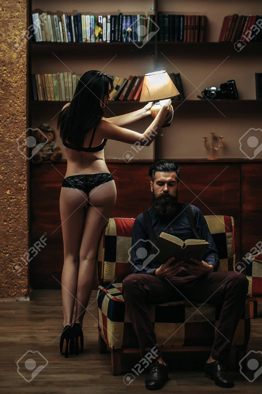 699ccc40ad5 Stock Photo - young couple of handsome bearded man sitting on armchair in  library reading book and pretty cute girl or woman in black lingerie with  sexy ...