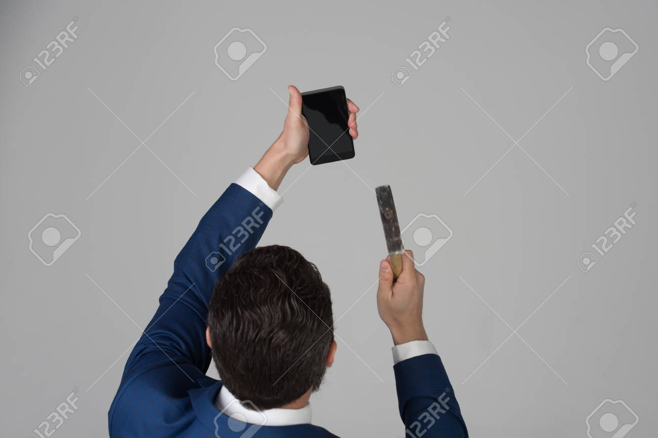 Businessman Or Man Crushing Mobile Or Cell Phone With Hammer Stock