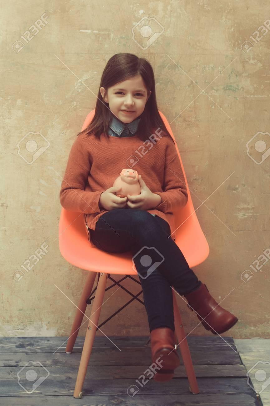 100% authentique e6f92 34a9f Investissement. Sourire, mignon, petit, petit, fille, enfant à la mode,  pull rouge et jeans bleu tenant une tirelire rose sur une chaise orange sur  ...