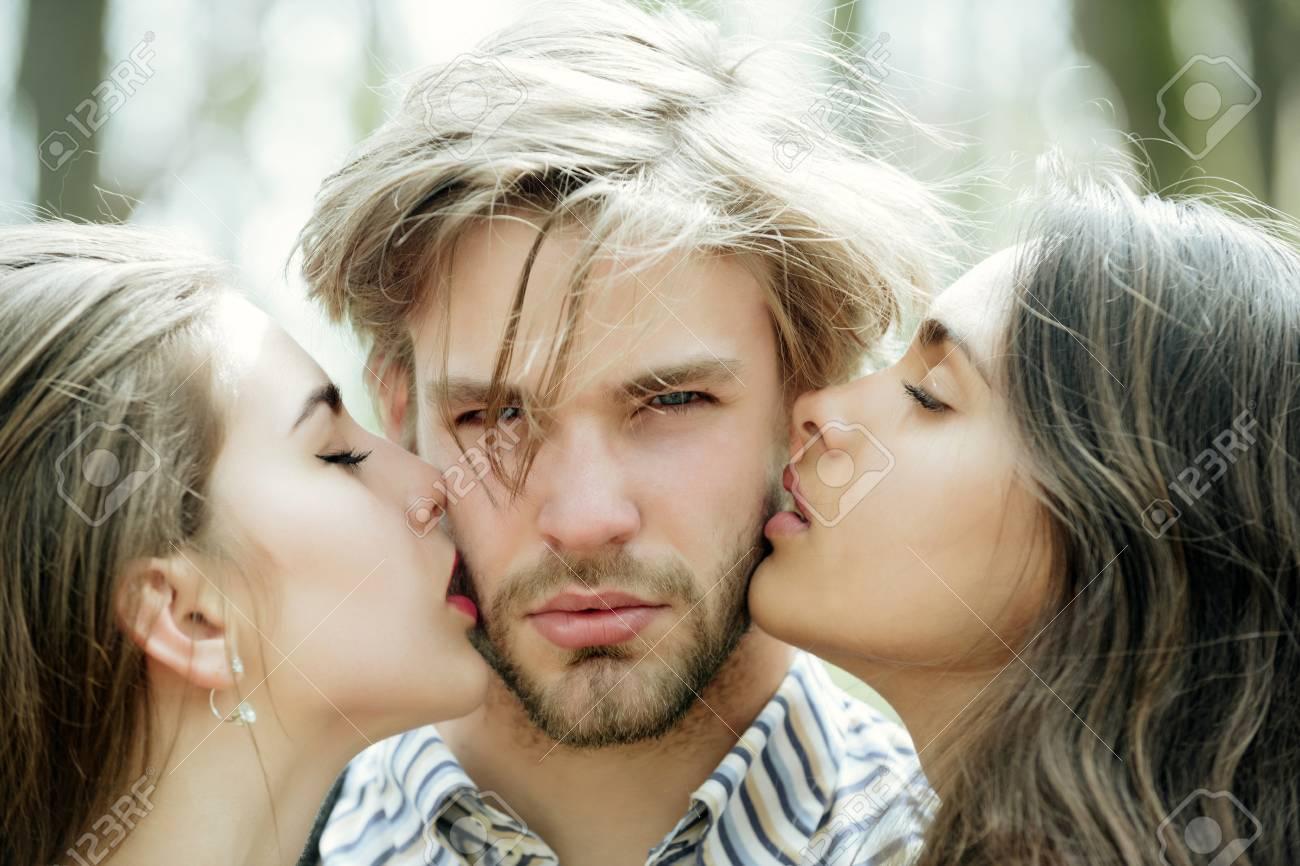 Hombre Que Consigue El Beso Por Dos Muchachas Bonitas O Mujeres Lindas En Día Asoleado En Fondo Natural Triángulo Amoroso Relación