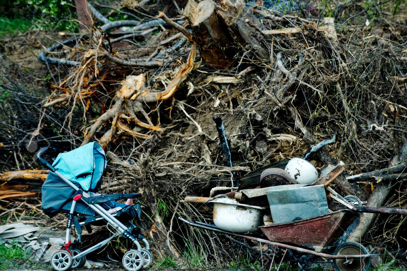 Heap of scrap or garbage dump of mixed, used rubbish, stroller,