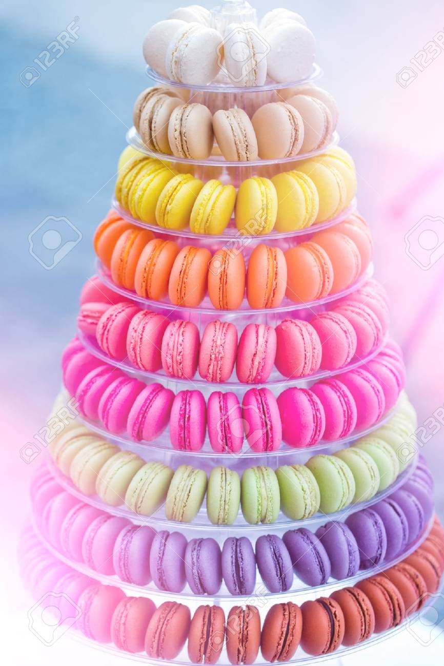 Colorful french macarons, multilevel cake pyramid, on plastic, dessert stand or plate on blurred background. Food, dieting. Birthday, anniversary, wedding celebration - 80037070