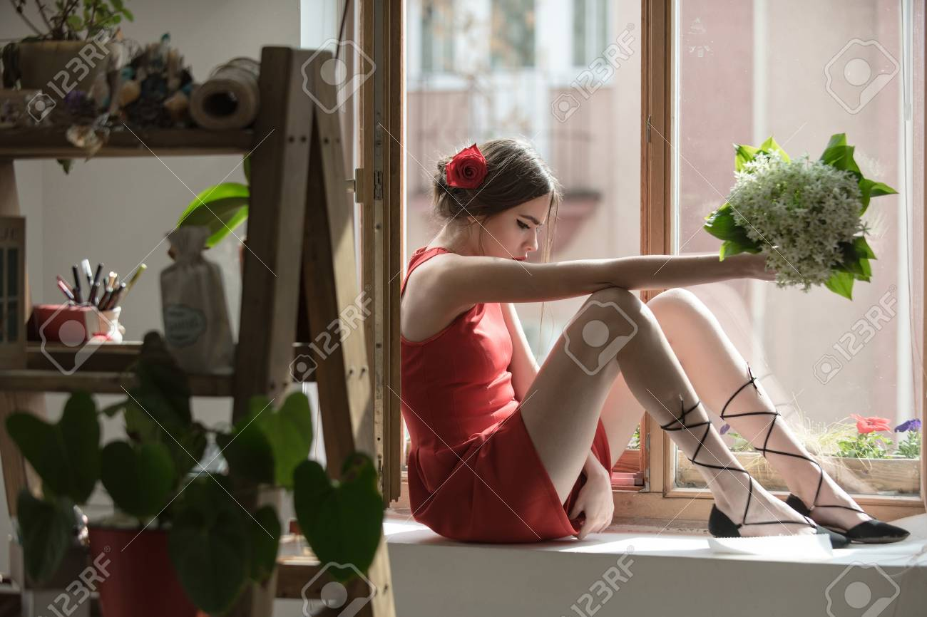 Young Girl In Red Dress And Rose Flower In Hair Sitting At Window ...