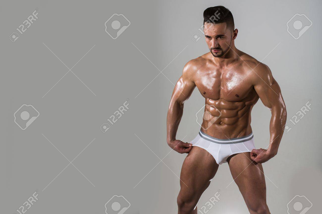 Muscular Man With Muscle Torso In Studio On Grey Background Stock