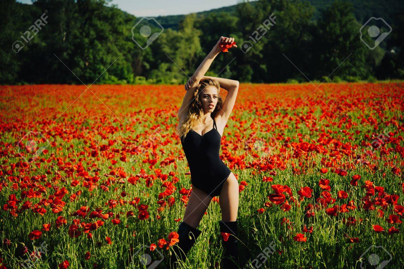 Woman With Long Curly Hair In Black Bodysuit In Flower Field Stock