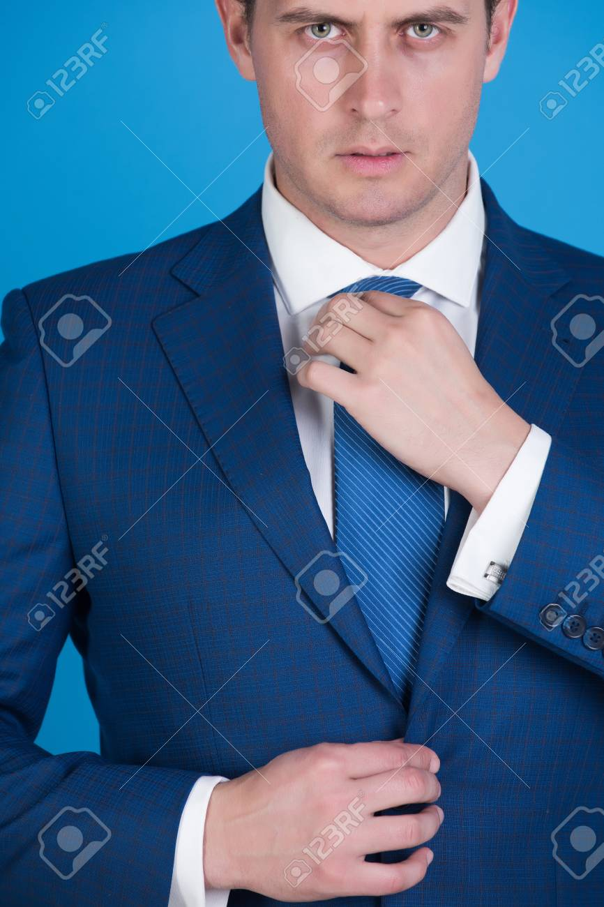325b46686 boss or confident businessman adjusting tie in elegant navy formal suit and white  shirt on blue