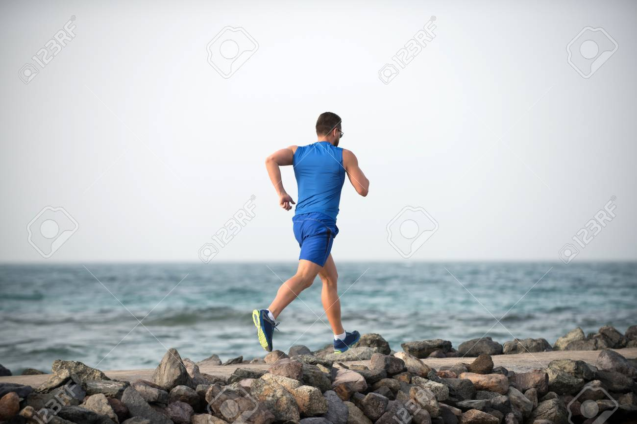 Back view running male athlete boy in blue sportswear with muscular strong body on stone coast of ocean in summer on background of sky and water - 81543244