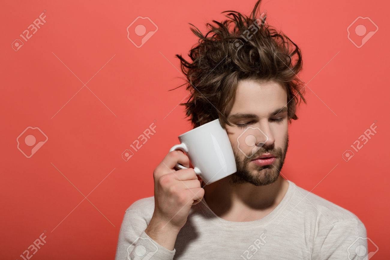 sleepy man with cup of tea or coffee has uncombed hair in underwear on red background, morning refreshment and drink, copy space - 82163542