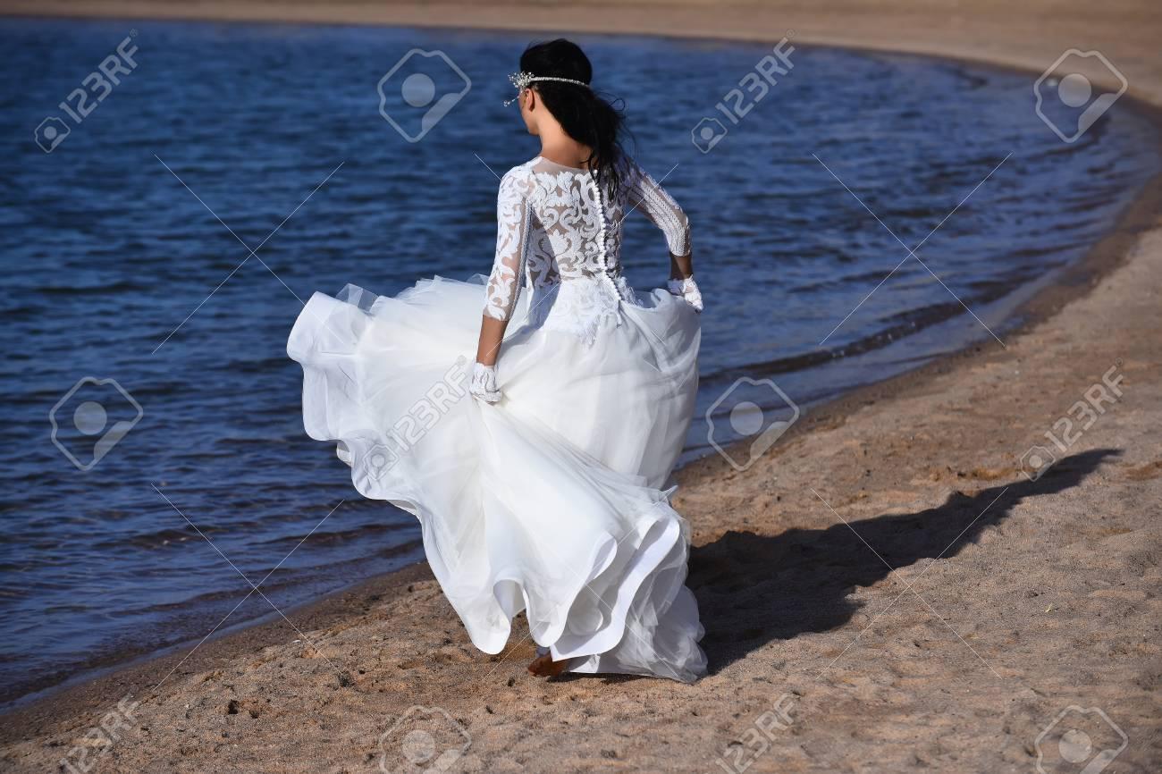 braut hübsche junge frau allein in weiß schöne hochzeit lange kleid barfuß  zu fuß entlang sand küste des blauen ozeans im freien
