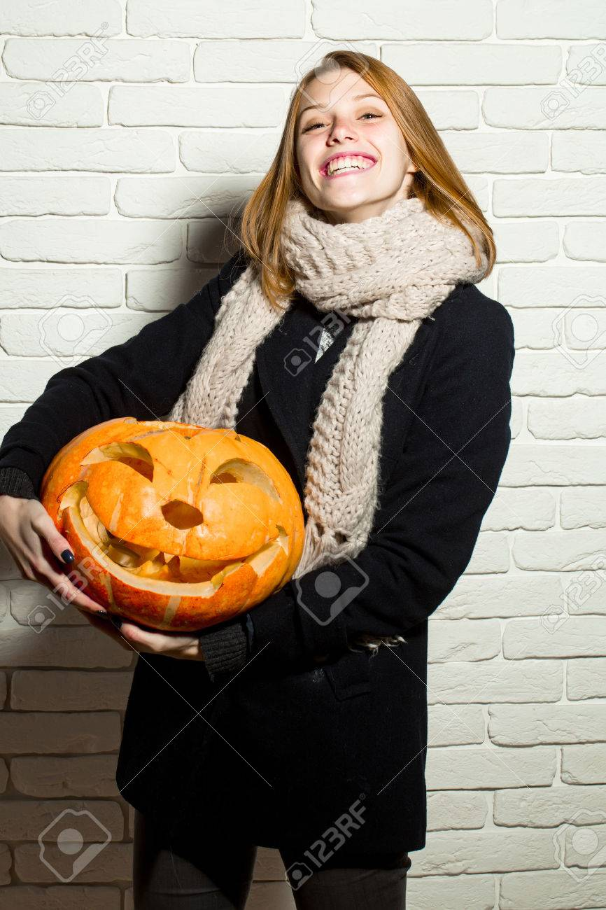 Halloween woman with happy face. Girl with orange scary pumpkin. Woman in coat and scarf at brick wall. Holiday and celebration. Party and traditional food. - 83652552