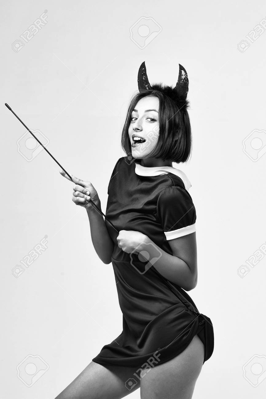 halloween woman or girl with smiling face in dress and devil horns or antlers holiday costume