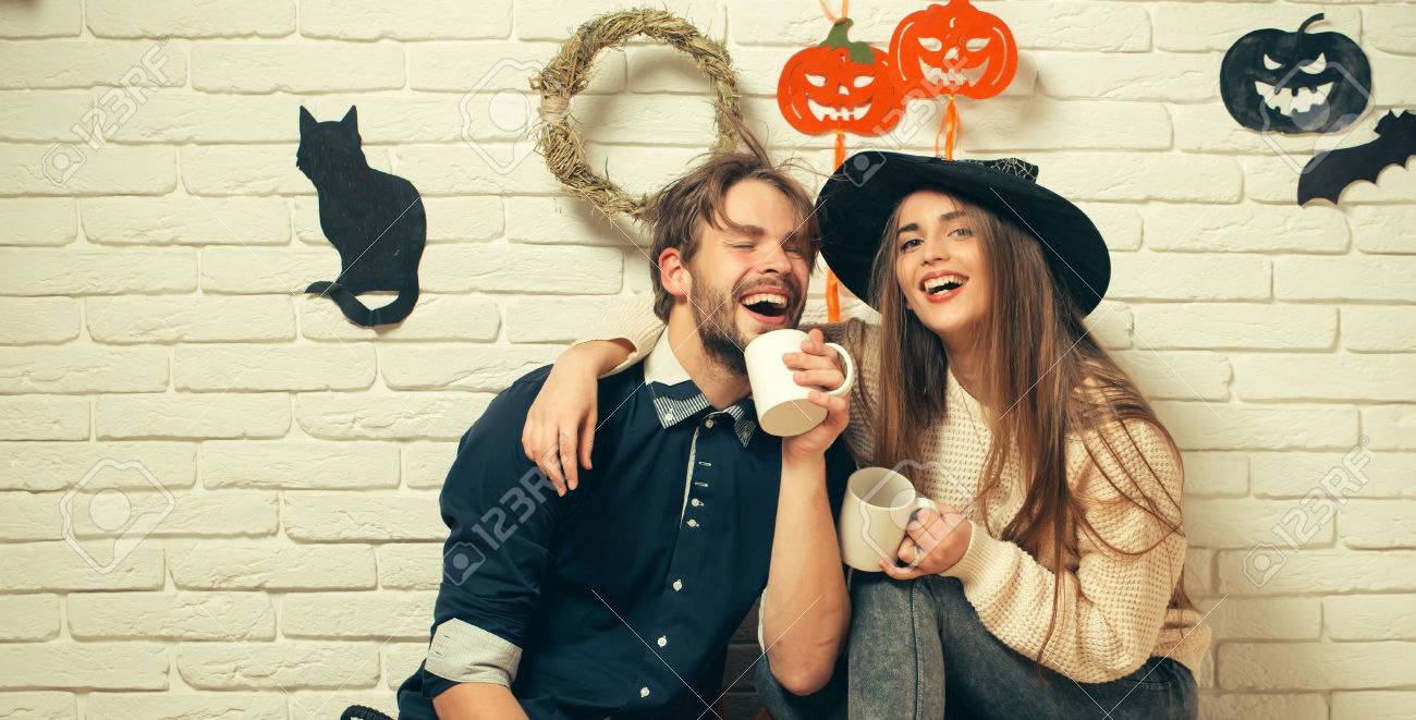 Halloween woman with long hair in witch hat. Happy couple in love with cups smiling. Man in casual wear sitting on floor. Holiday traditional symbols on white brick wall. Celebration and party concept - 84366260