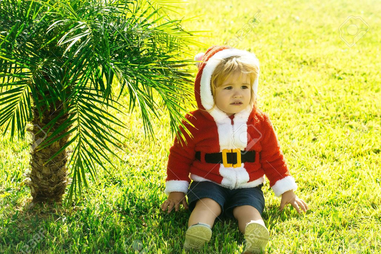 ff20c73a4f8c Baby Boy In Santa Claus Costume Sitting At Palm Tree On Green ...