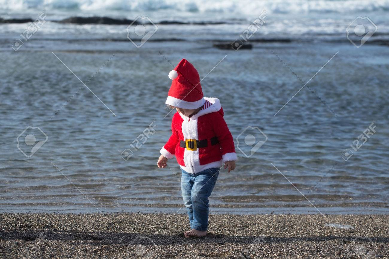 Kid in santa costume walking barefoot on sea beach on sunny summer day on natural background & Kid In Santa Costume Walking Barefoot On Sea Beach On Sunny Summer ...