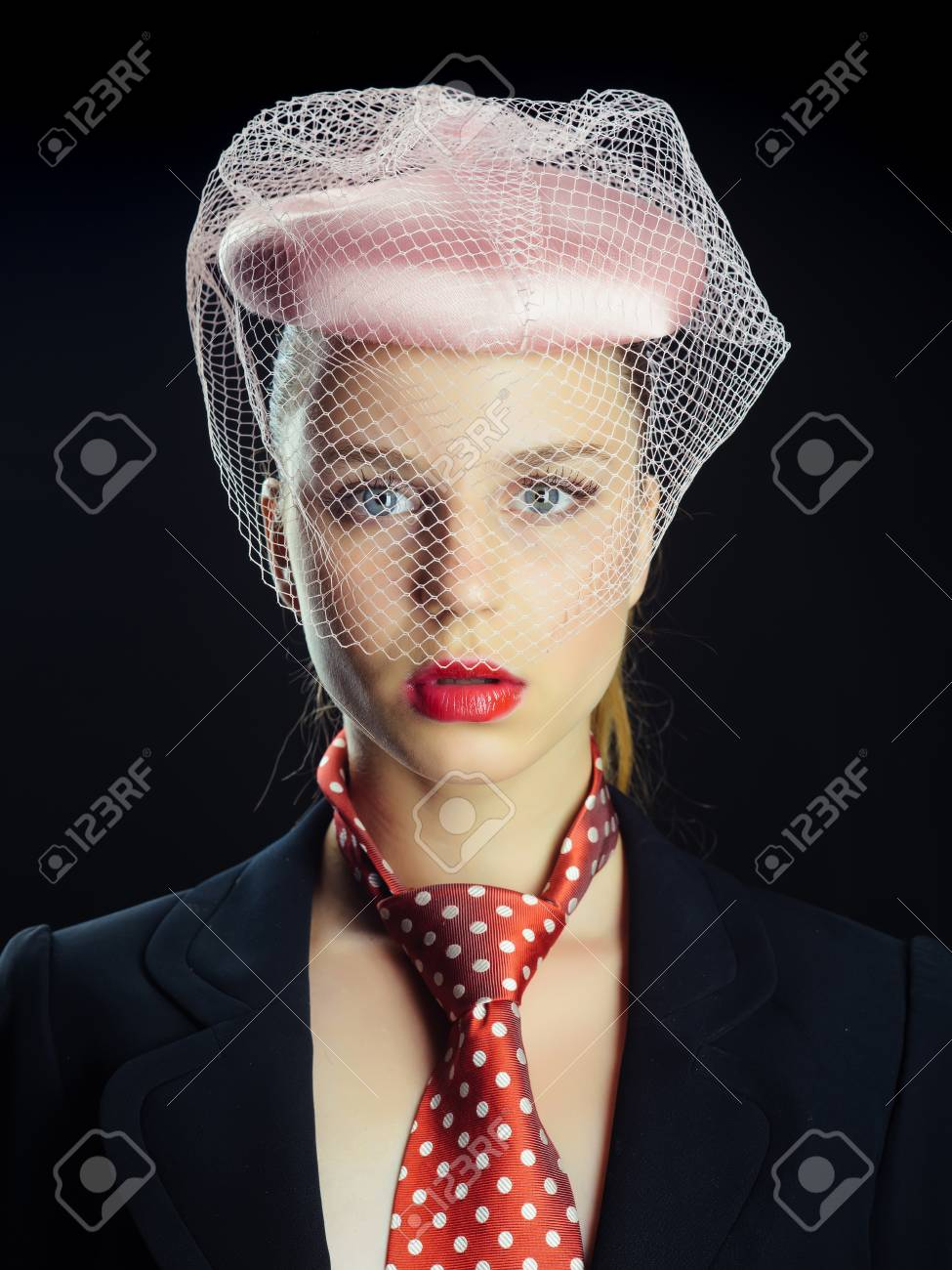 Stock Photo - Woman wearing pink hat with veil. Girl in tie with red dots  on neck. Lady posing on black background. Retro or vintage style concept. 1638551b4f8a