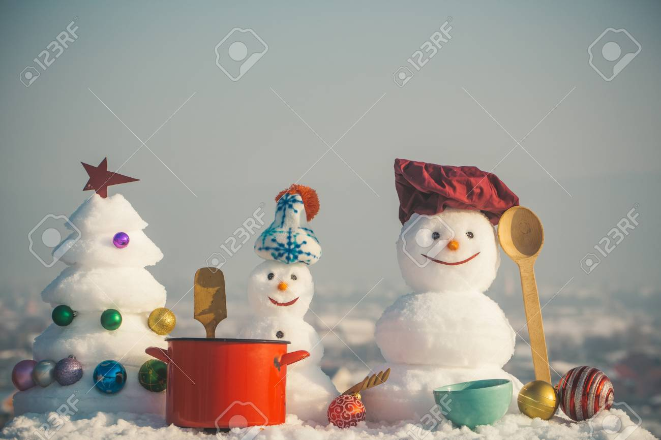 Arbre En Pot Hiver chef de noël bonhomme de neige en chapeau avec pot rouge, cuillère en bois  et une fourchette au ciel bleu en hiver près de nouvel an arbre et jouets
