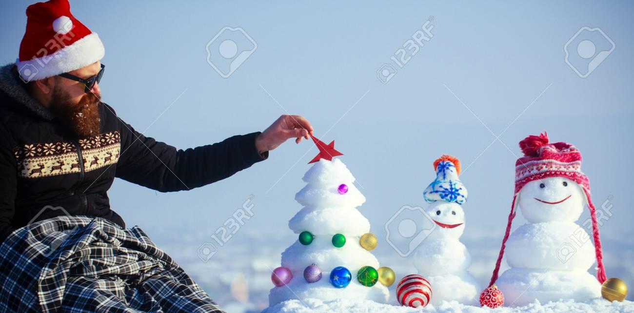 santa man putting red star on snow xmas tree hipster in santa