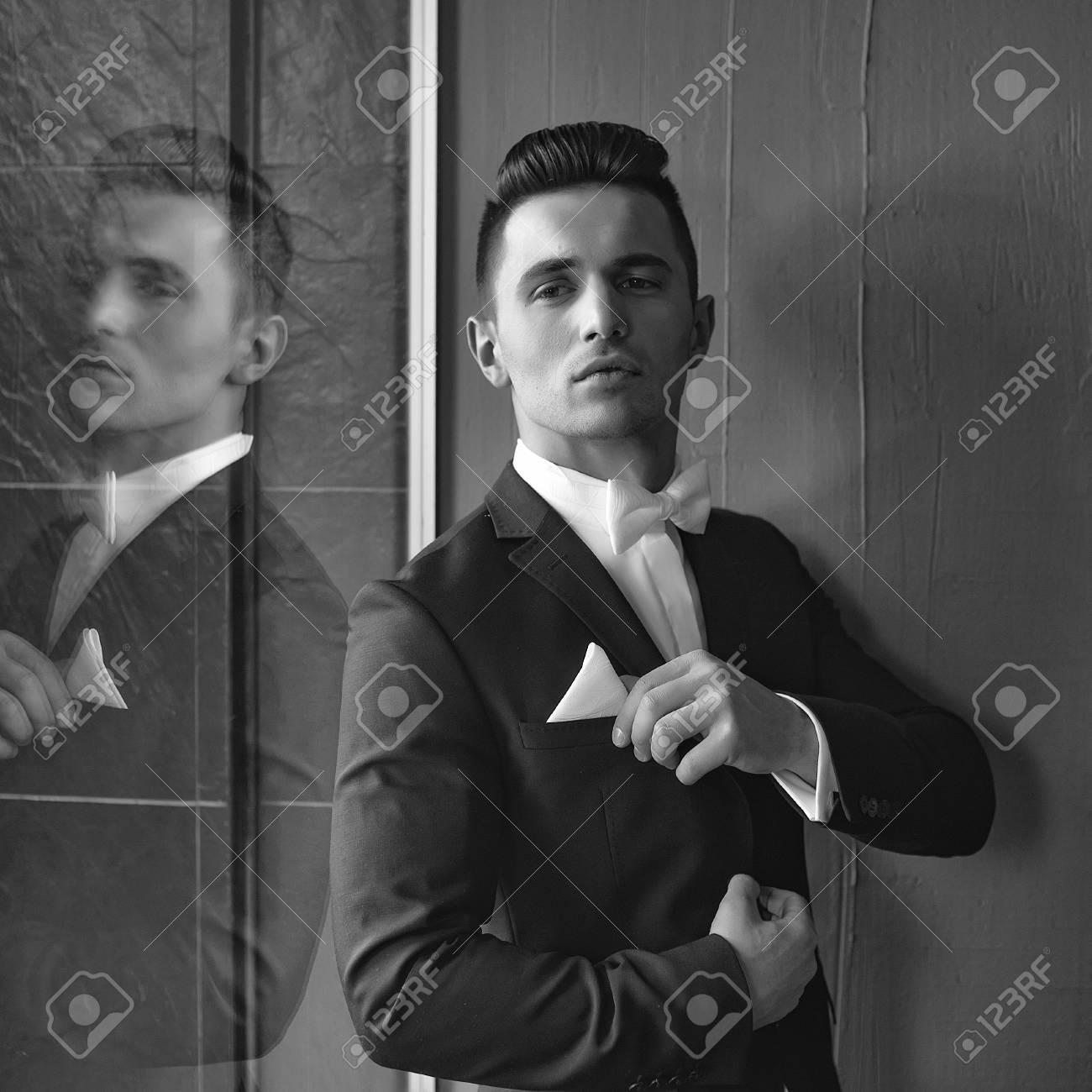 4fd8aacf8226c El hombre en traje con corbata de lazo blanco toca pañuelo joven con estilo  elegante se