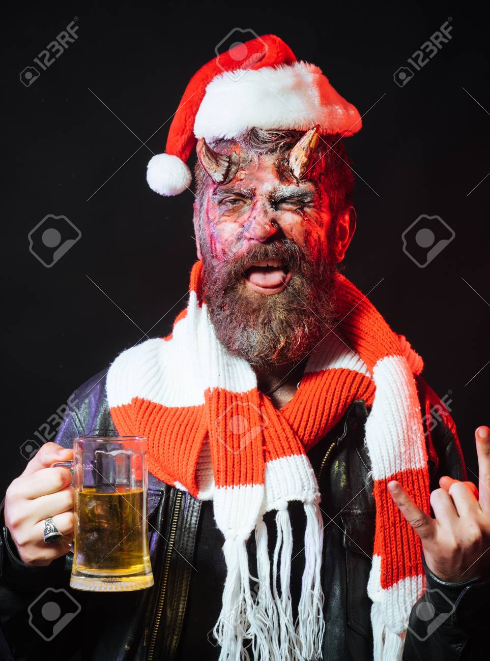 2960ccc9e51df Halloween christmas devil in santa hat and scarf. Man demon drink beer on  black background