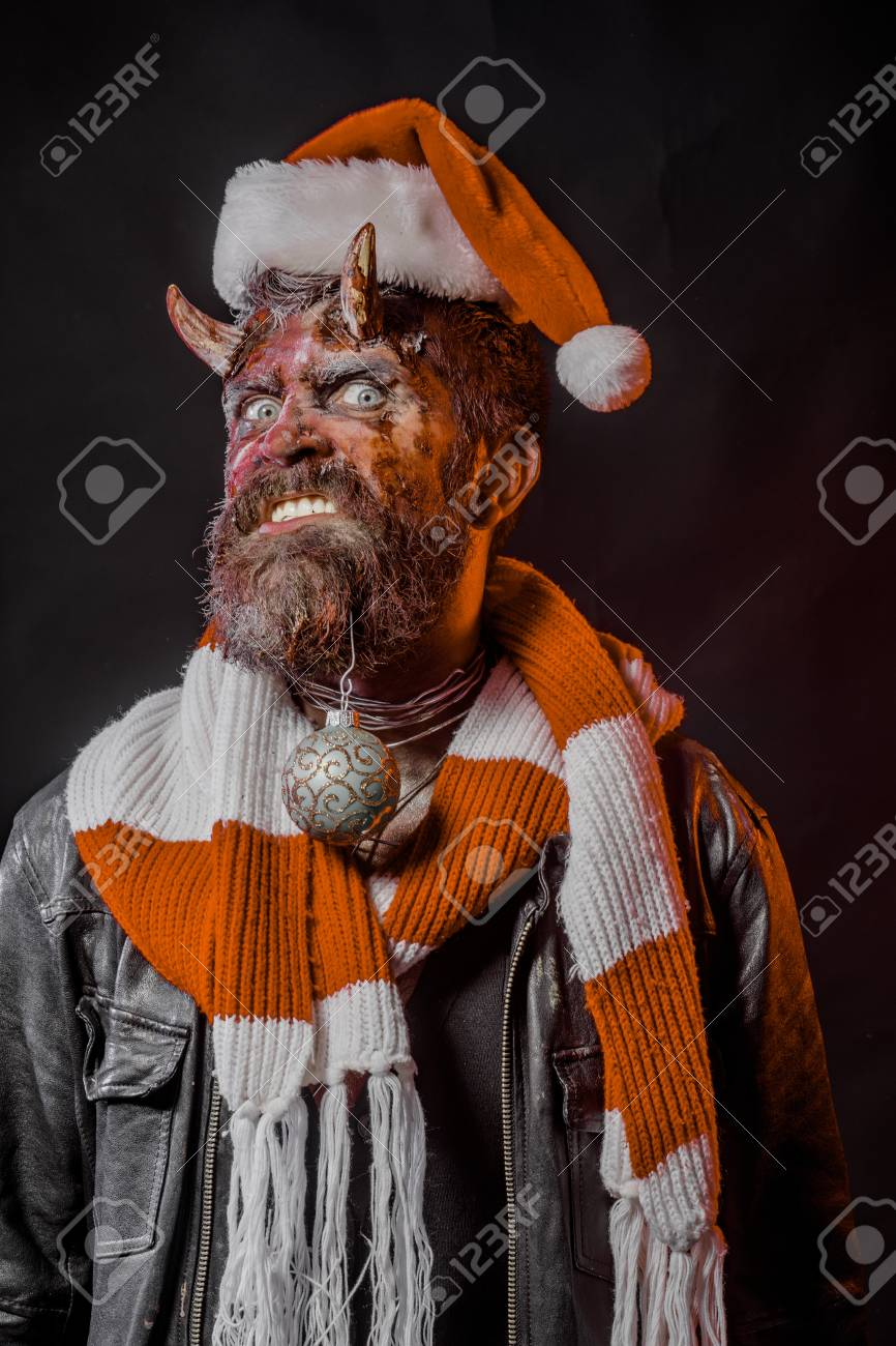 737a0b431ed67 Halloween christmas or new year man with devil horns in santa hat and scarf  green on