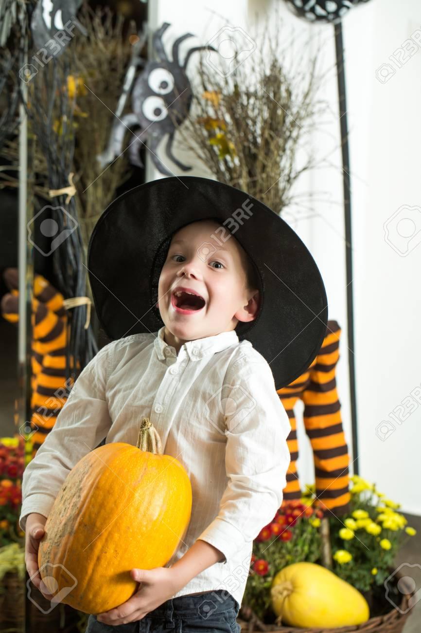 Bambino di Halloween con il volto felice. Piccolo ragazzo in cappello a  ragnatela a calze a righe. Bambino con zucca arancione in cappello da  strega. 433e041877e4
