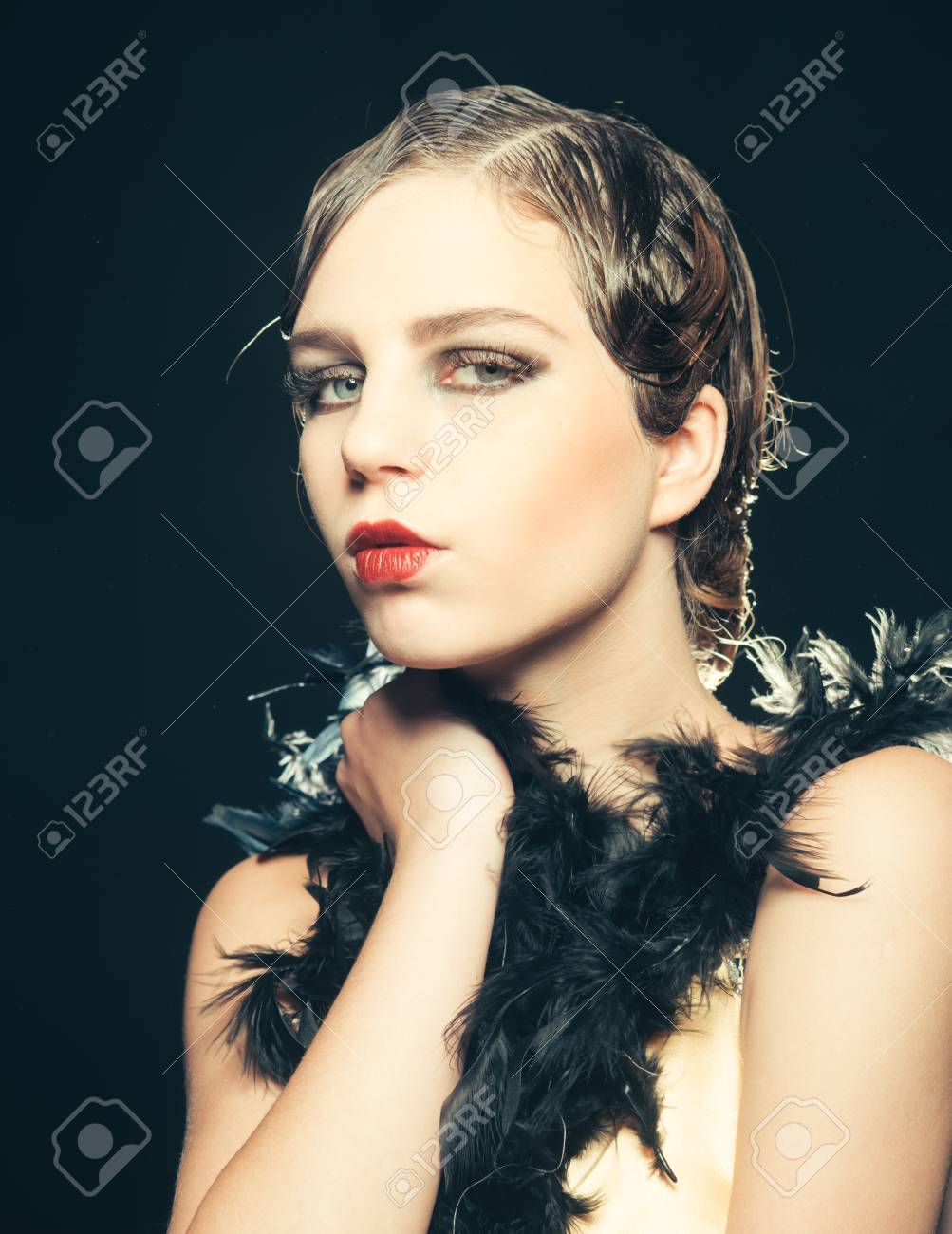 pinup girl in boa with retro hair and makeup on black background,..