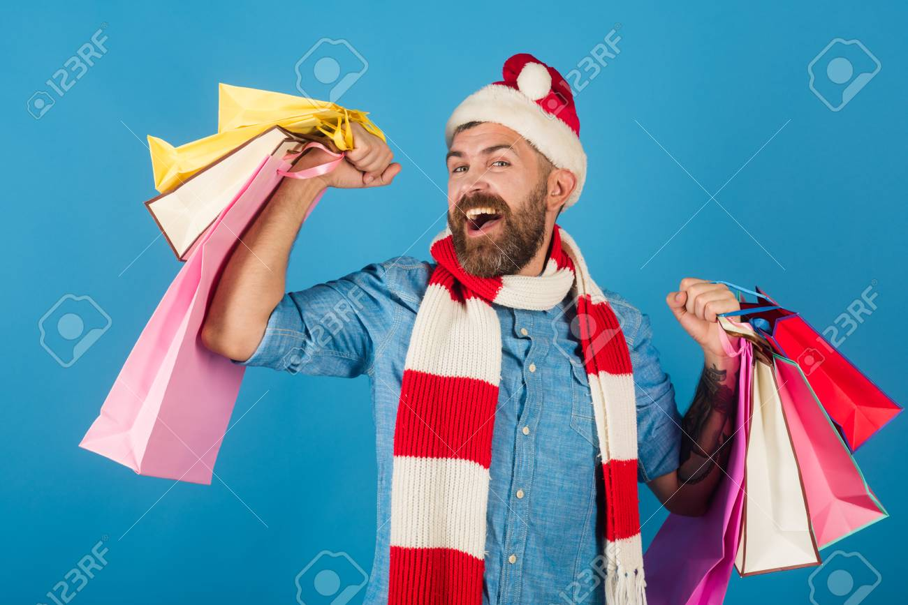 89fcb34f38651 Black friday sale concept. Christmas man shopper happy smile in santa hat  and scarf. Hipster hold shopping bags on