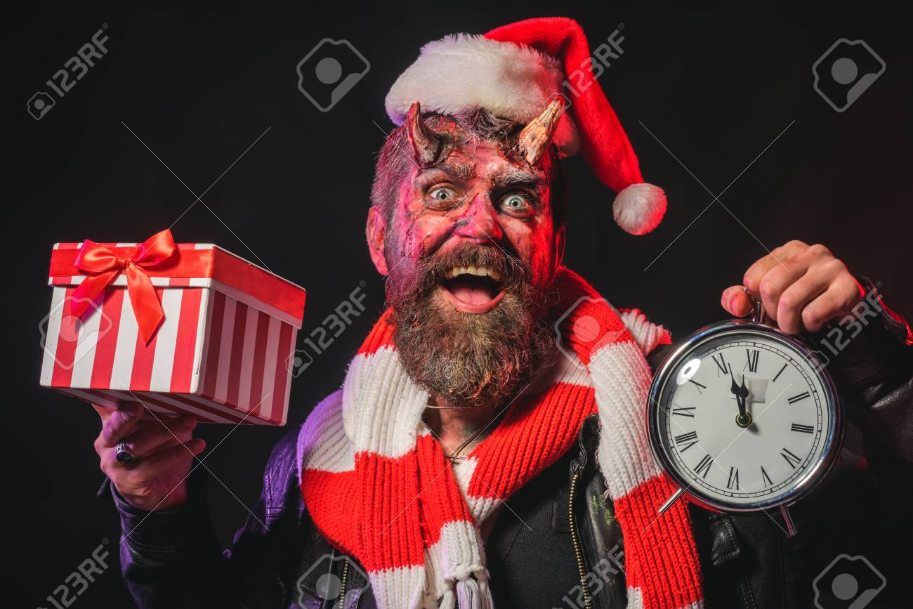 e2a71d2f55477 Halloween or christmas man devil hold present box and clock. Hipster smile  with satan horns