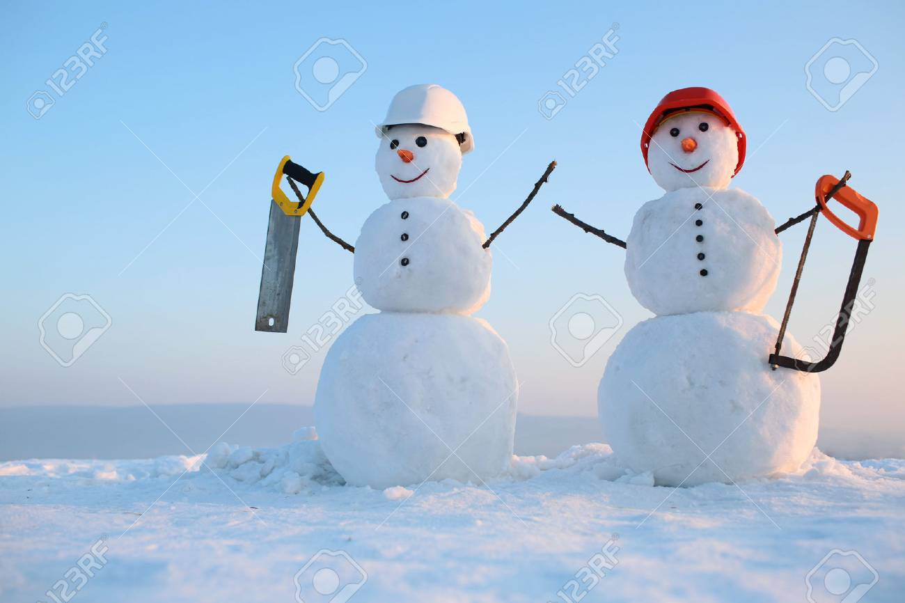 Christmas or xmas decoration. New year snowman from snow with saw. Building and repair work. Happy holiday and celebration. Snowman builder in winter in helmet. - 90704846